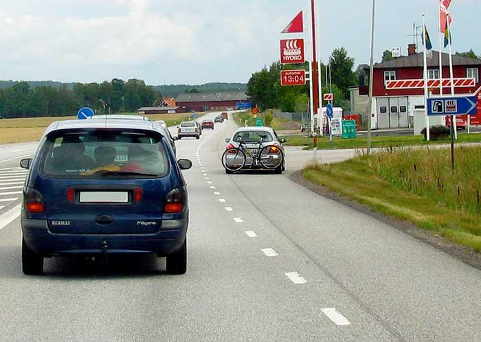 Bil som kör ut på vägrenen innan sväng. Sikten är mycket god.