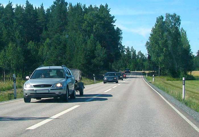 Landsväg med bilar som håller för kort avstånd till varandra.